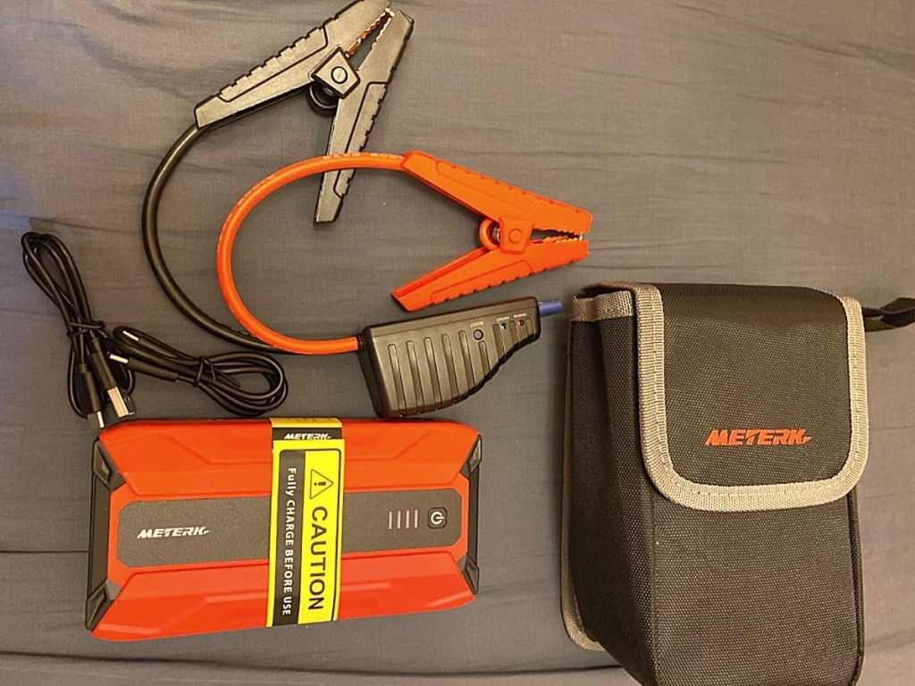red and black portable jump starter kit with cables and bag