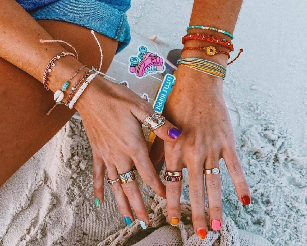 pura vida rings and bracelets on hands