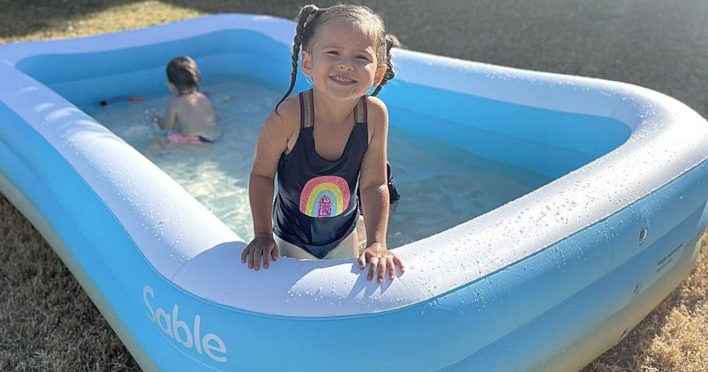 little girl standing in Sable inflatable pool
