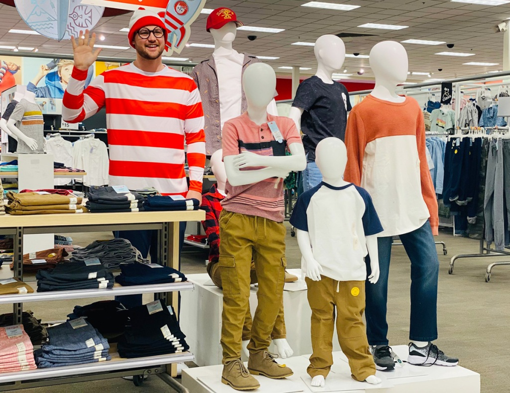 man posing with mannequins at target