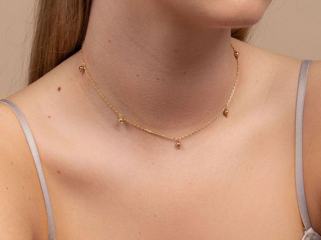 woman wearing gold necklace