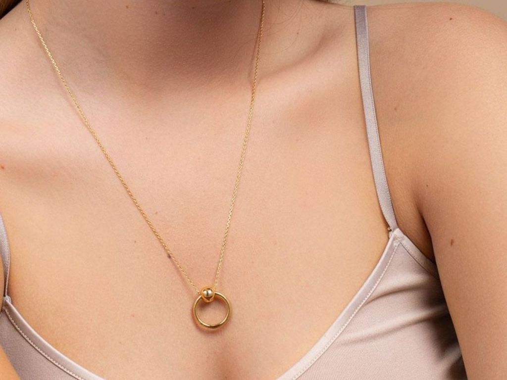 woman wearing circle gold necklace