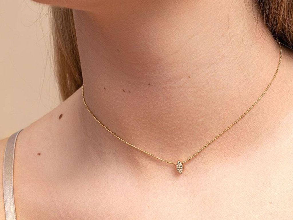woman wearing gold necklace with diamond shape gem