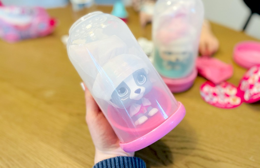 hand holding clear bottle with plastic toy inside