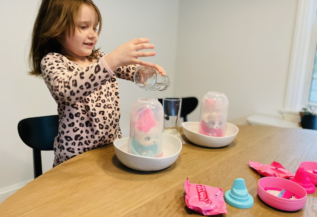 girl dumping water on surprise toy