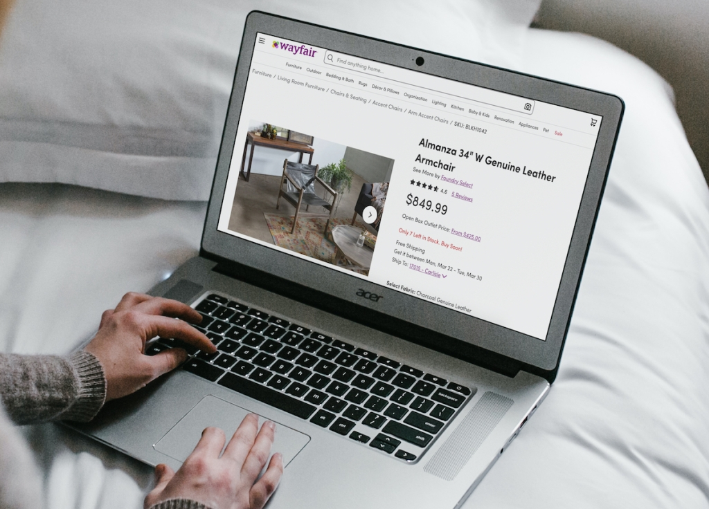 hands typing on laptop with wayfair chair listing on screen home decor ideas