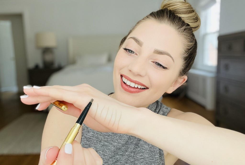 woman holding unibrow universal eyebrow pencil up to hand drawing lines