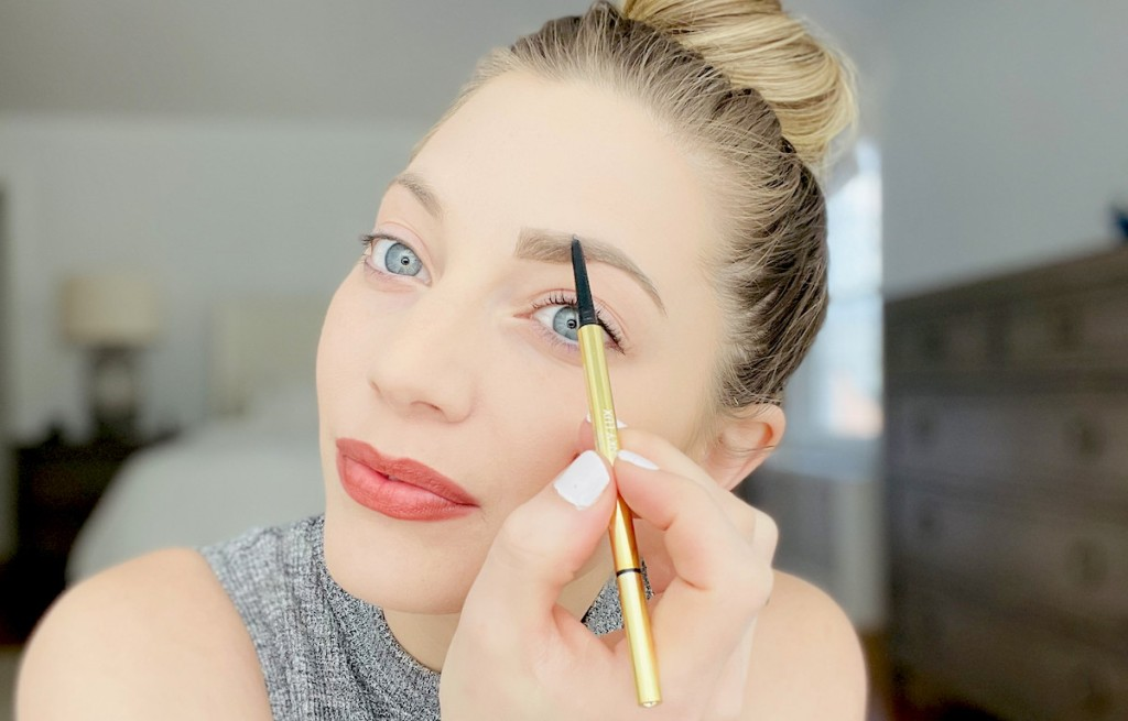 close up of woman doing eyebrows with gold winky lux unibrow pencil