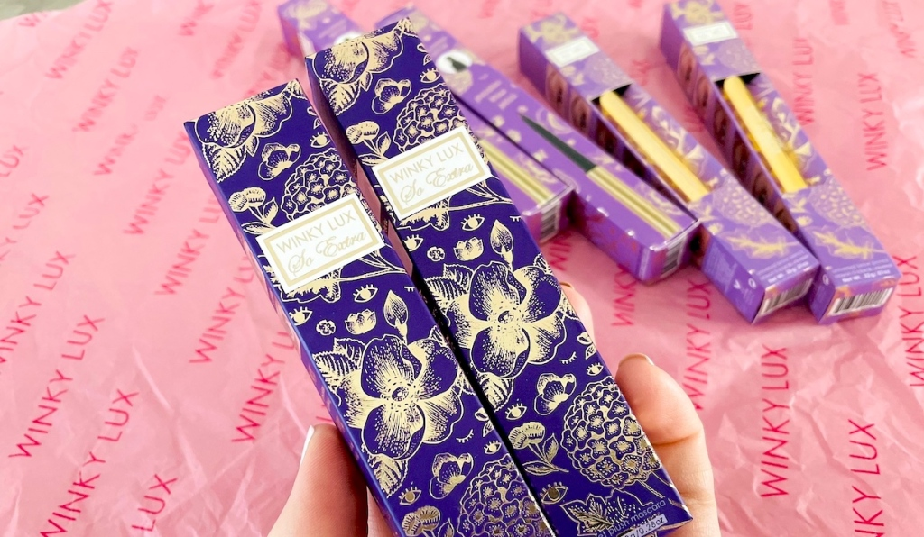 hand holding two purple boxes of winky lux mascara