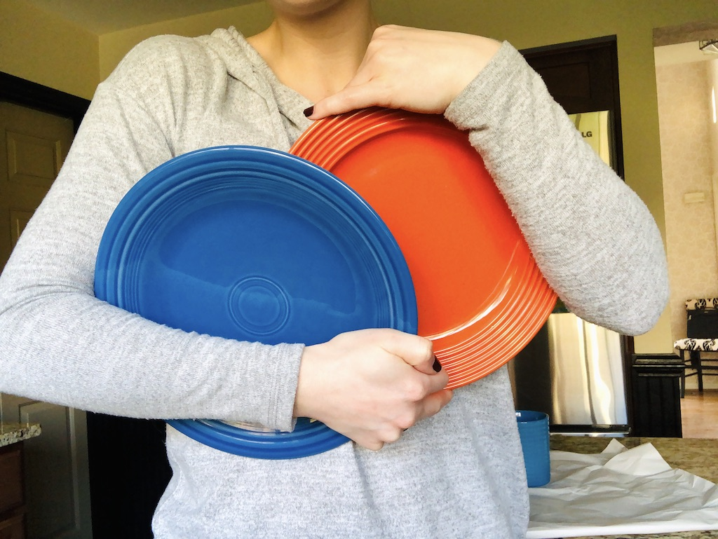 woman holding Dollar Tree plates in kitchen