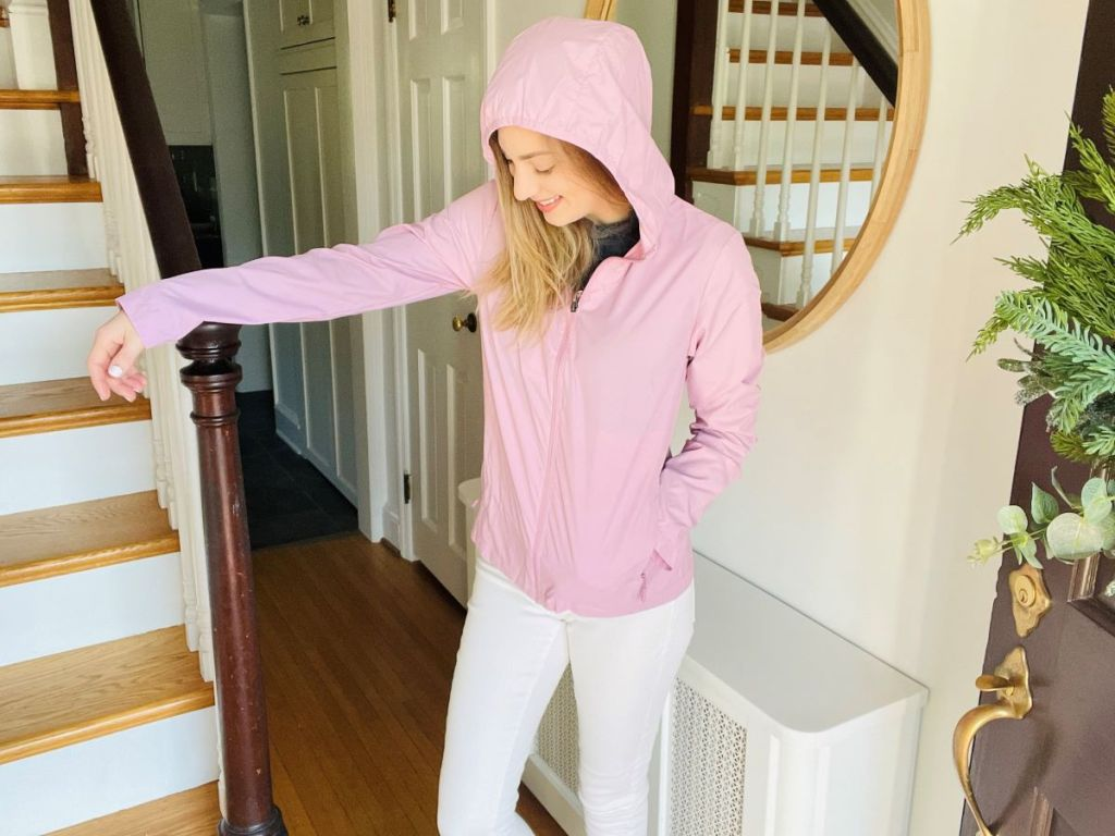 woman wearing a pink jacket standing next to stairs