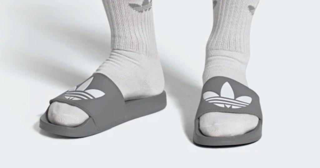person wearing adidas grey slides