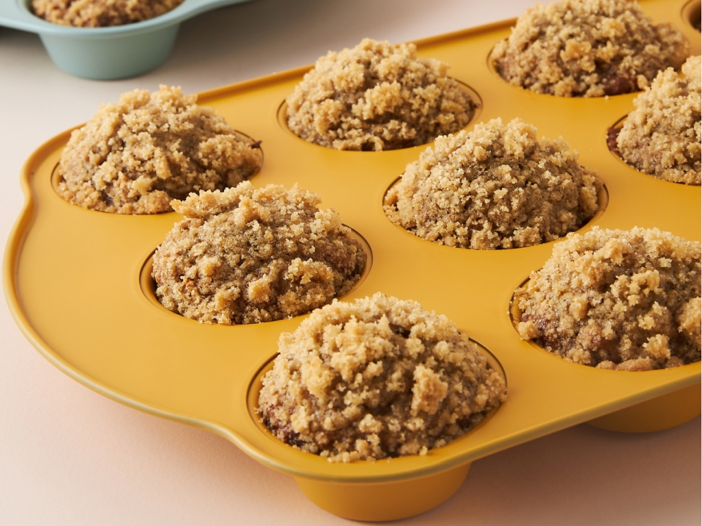 Muffin tin in orange color with muffins inside