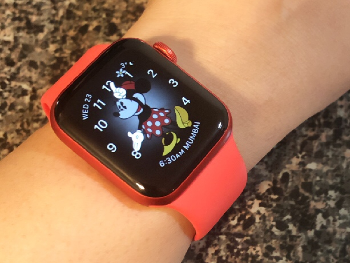 red apple watch worn on wrist with minnie mouse face