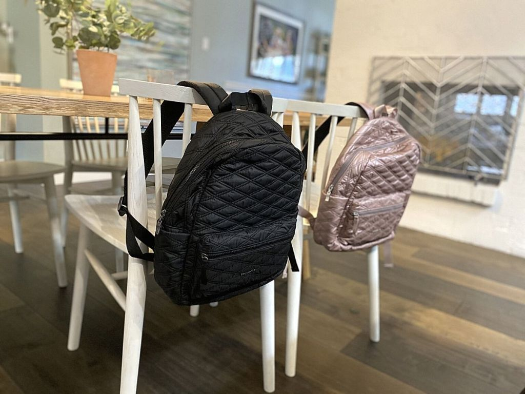 baggallini backpacks hanging on chairs in a dining room