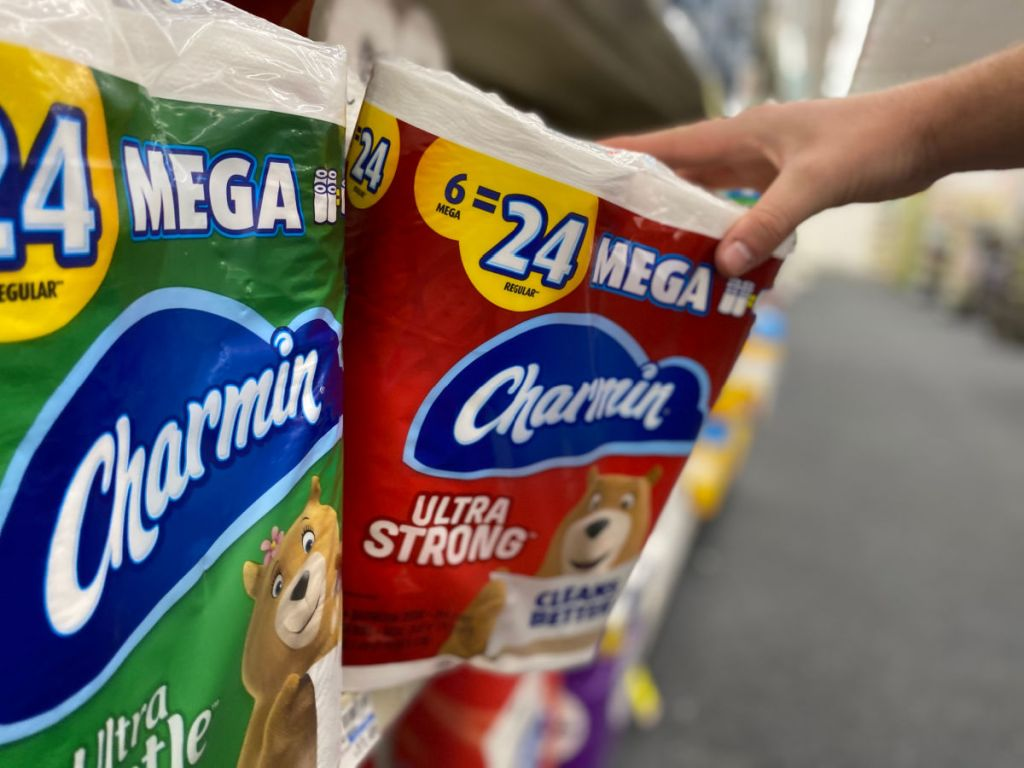 Person grabbing package of Charmin 6 Mega Rolls from store shelf