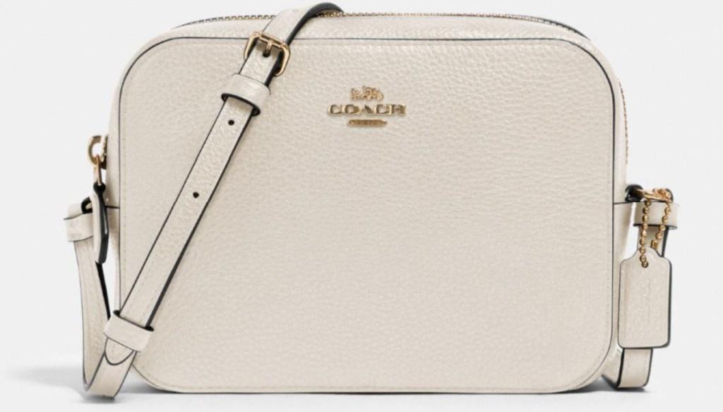 cream colored mini coach camera bag
