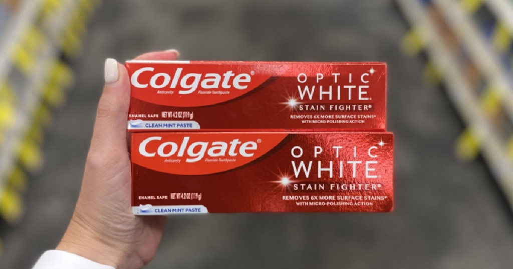 hand holding two red boxes of toothpaste