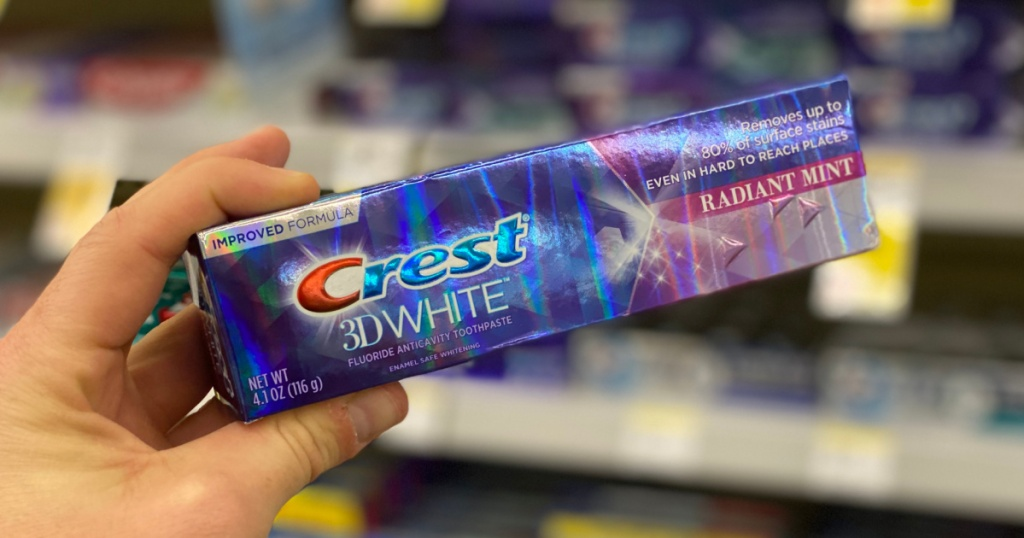 Hand holding tube of toothpaste