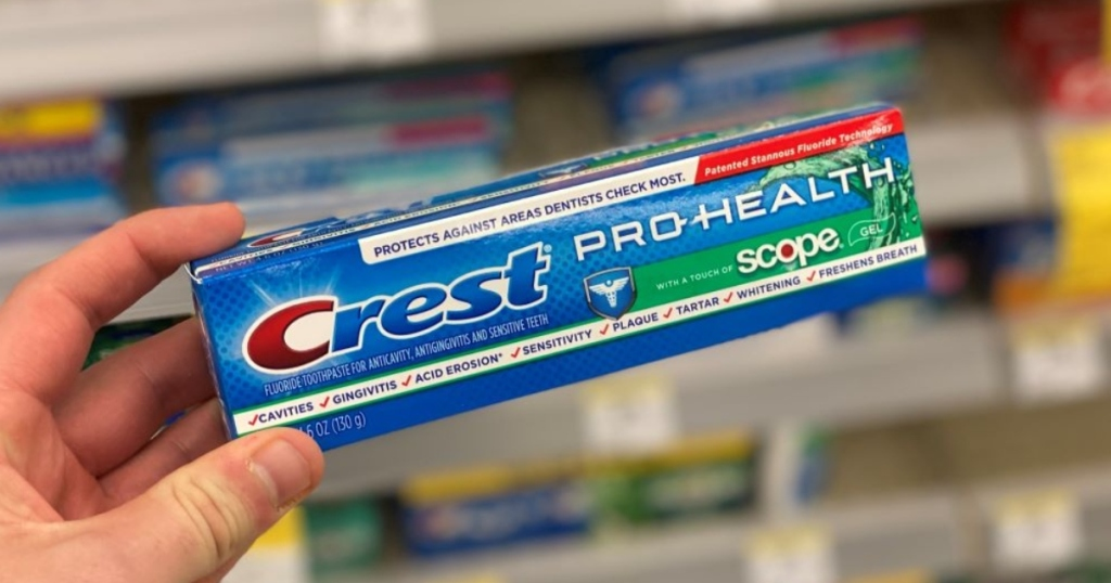 holding Crest toothpaste in box