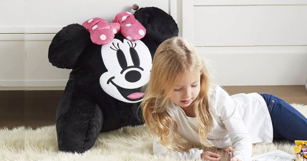 girl on floor next to a minnie mouse backrest pillow