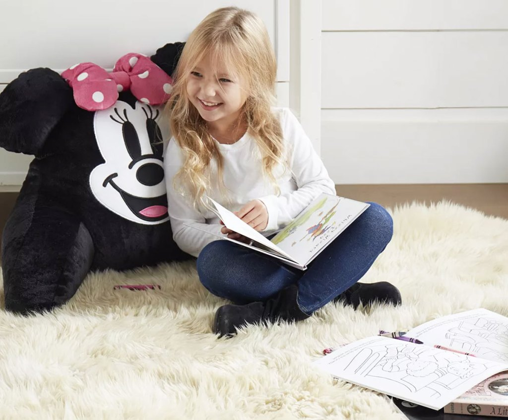 girl leaning against minnie mouse backrest pillow