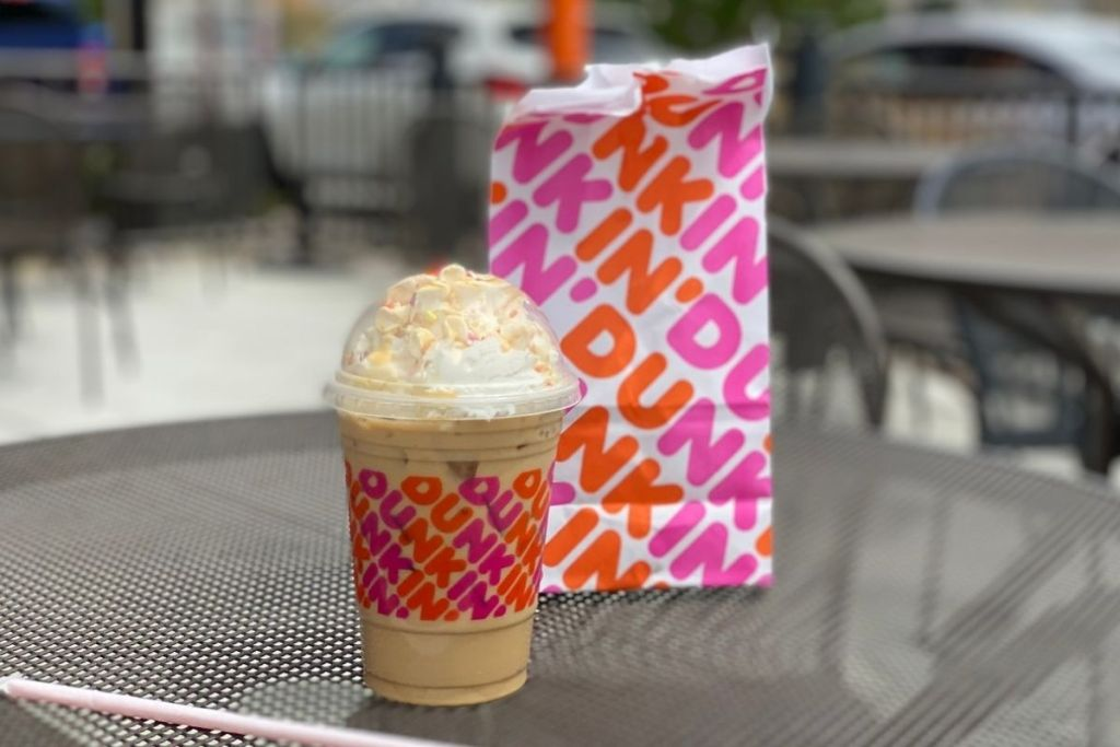 Dunkin' Butter Pecan Sundae Signature Iced Latte with a dunkin bag on an outdoor table