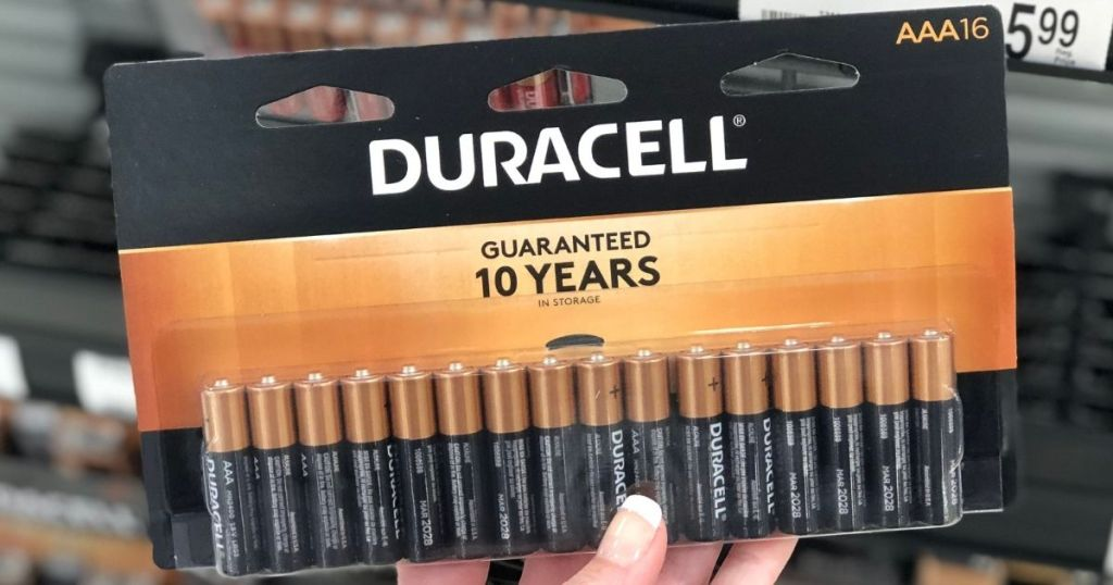 hand holding a package of Duracell batteries