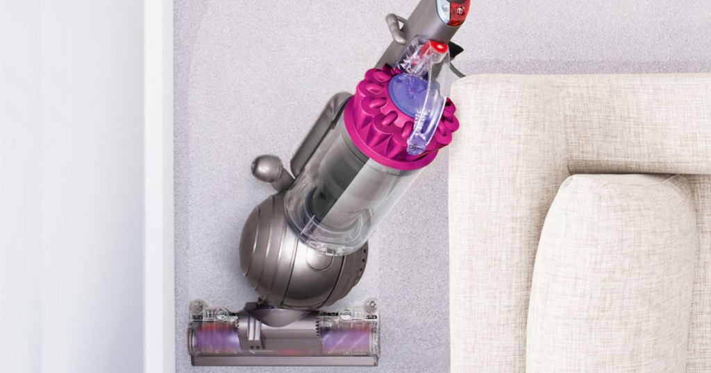 pink and grey dyson vacuuming around a couch