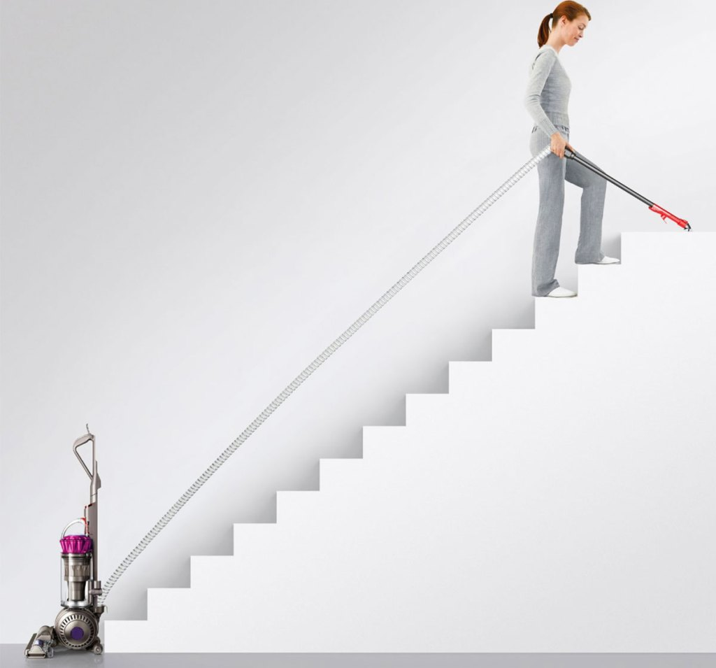 woman using dyson to clean stairs