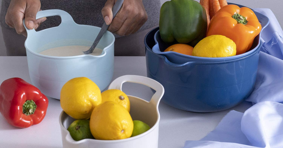 mixing bowl set with various fruits and vegetables with a pair of hands mixing liquid in one