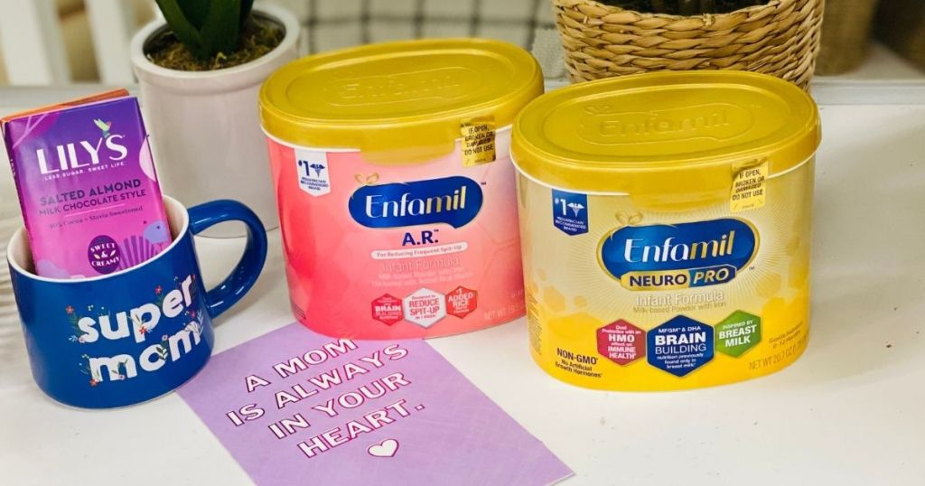 two infant formulas by a card and mug