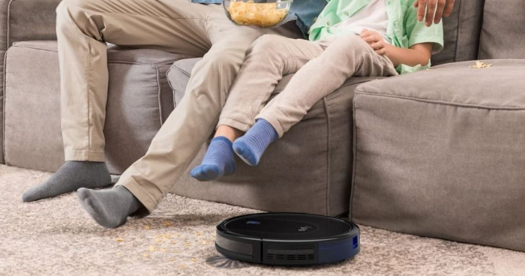 people on couch lifting up legs to let robotic vacuum pass on floor