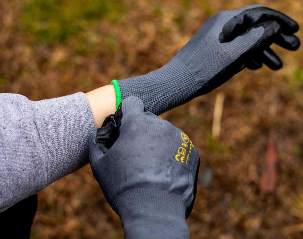 person putting on black gardening gloves