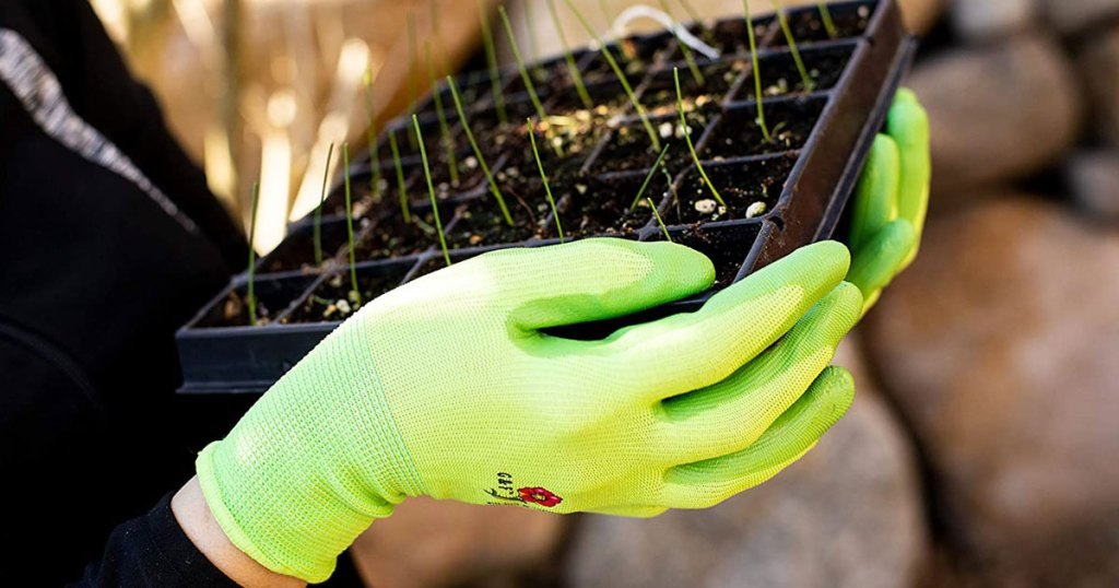 person wearing green gardening gloves