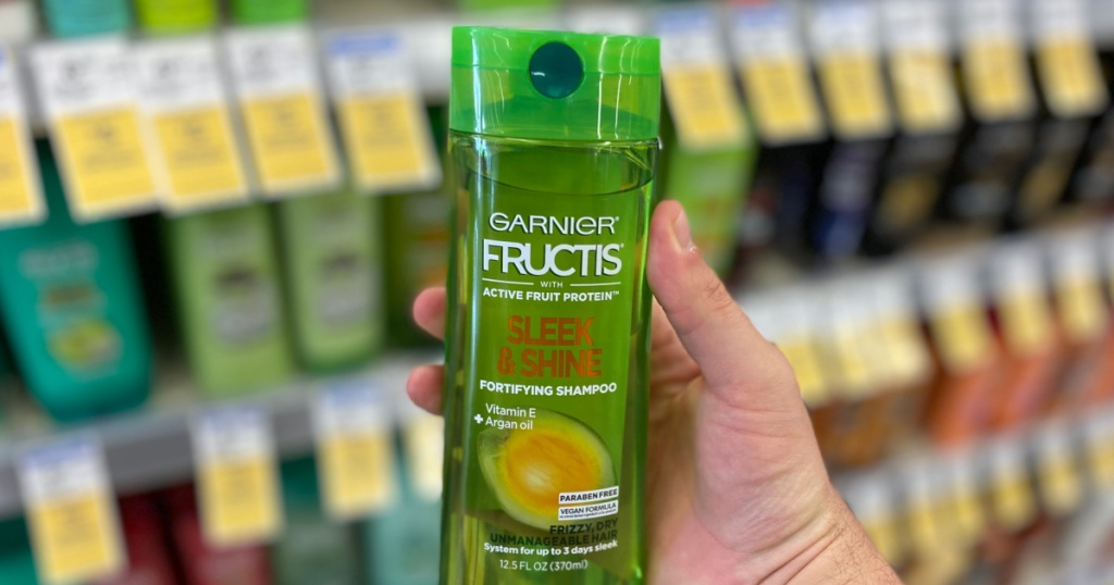 hand holding green bottle of shampoo