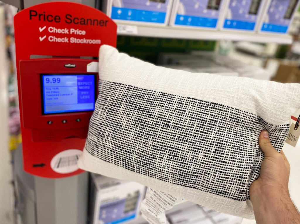person scanning a throw pillow at target price checker