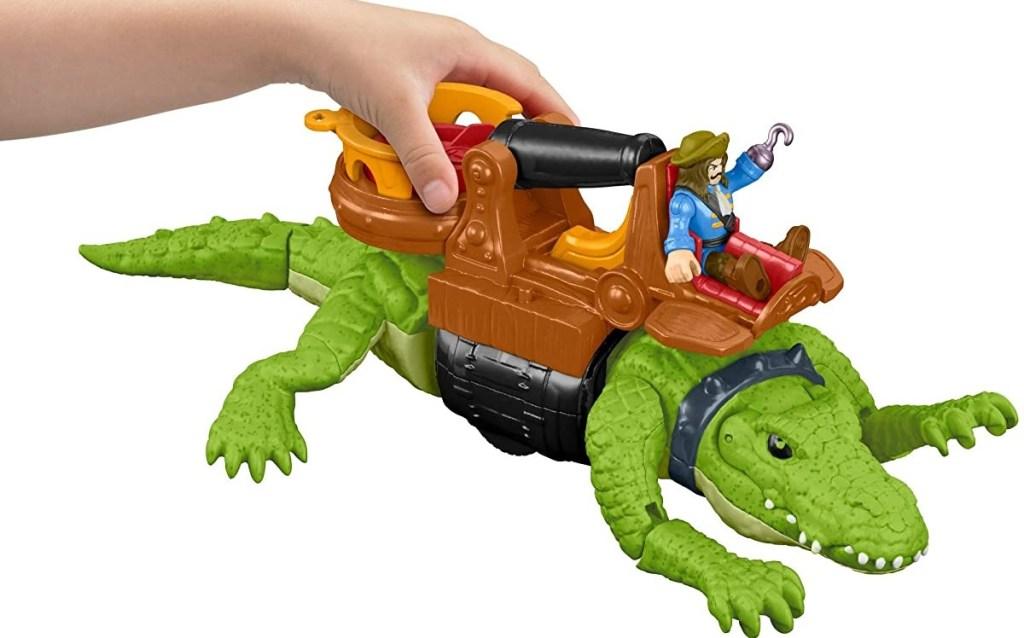 hand holding a toy crocodile