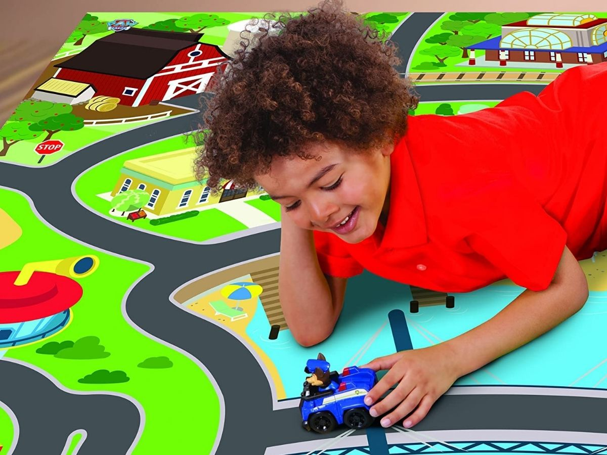 boy playing with paw patrol toy on playmat