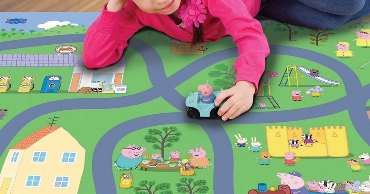 girl playing with peppa pig toy on playmat