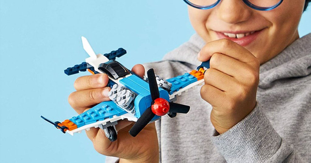boy playing with a lego propeller plane