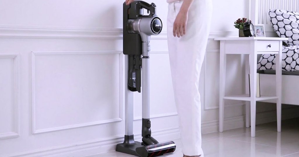 woman grabbing a stick vacuum from charging base