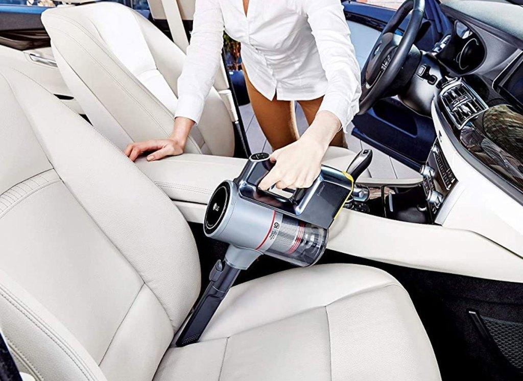 woman using handheld vacuum to clean car