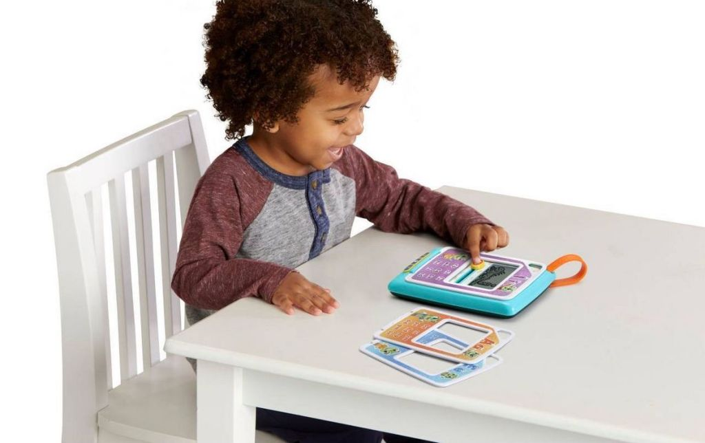 kid playing LeapFrog Phonics game in table