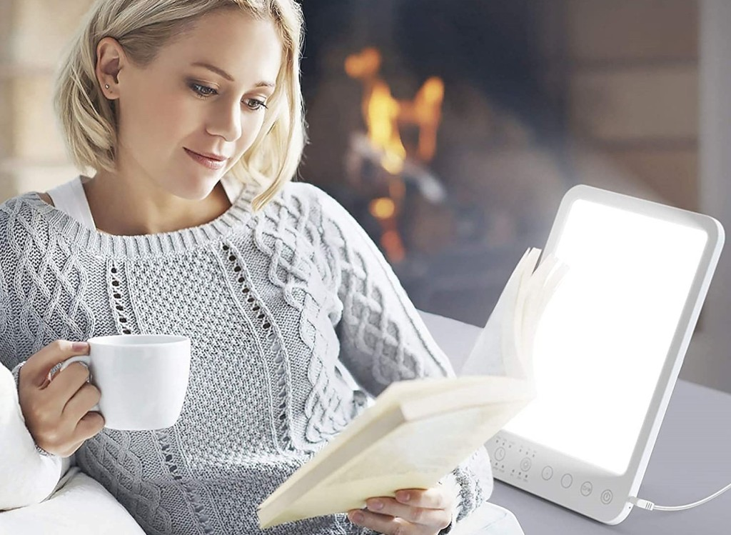 woman reading a book next to a lamp