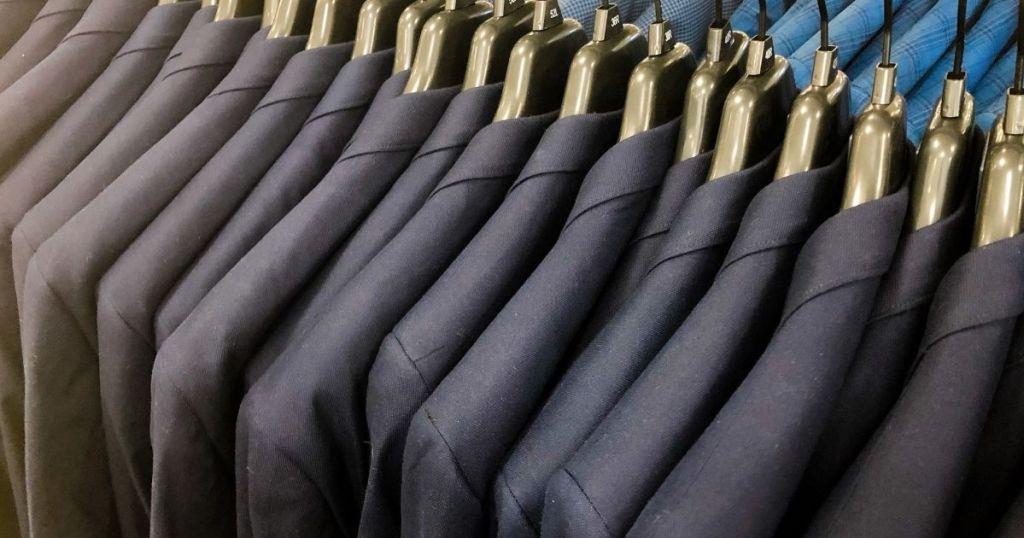 row of men's suits on hangers