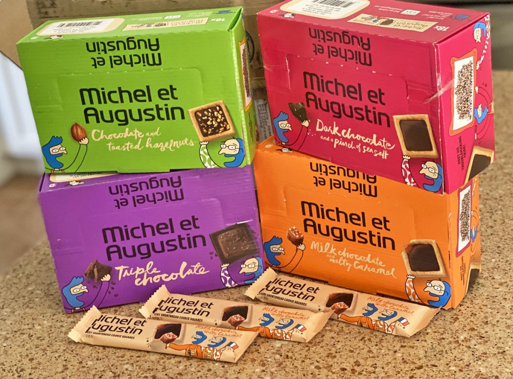 four colorful boxes of Michel et Augustin Gourmet Chocolate Cookie Square bars