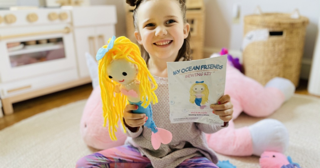 little girl holding mermaid plush doll and booklet