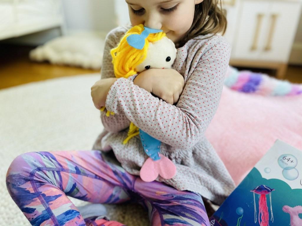 girl hugging plush mermaid doll
