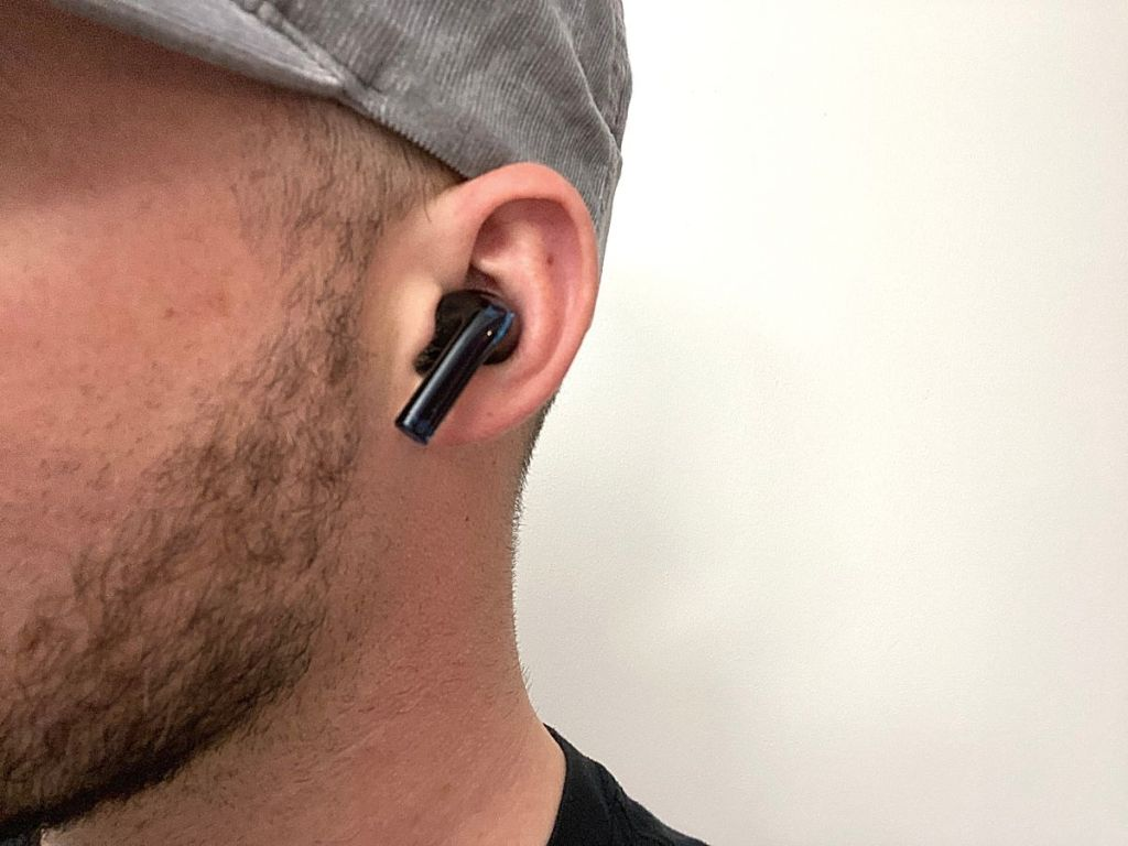 close up of man wearing black earbud in his ear